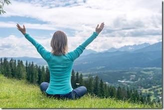 une femme fait de la méditation contemplative dans la nature