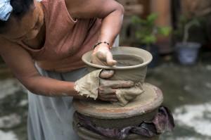une femme tourne un pot en argile