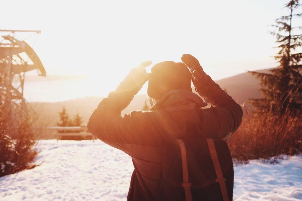 astuce anti-déprime hivernale : un homme profite du soleil en hiver