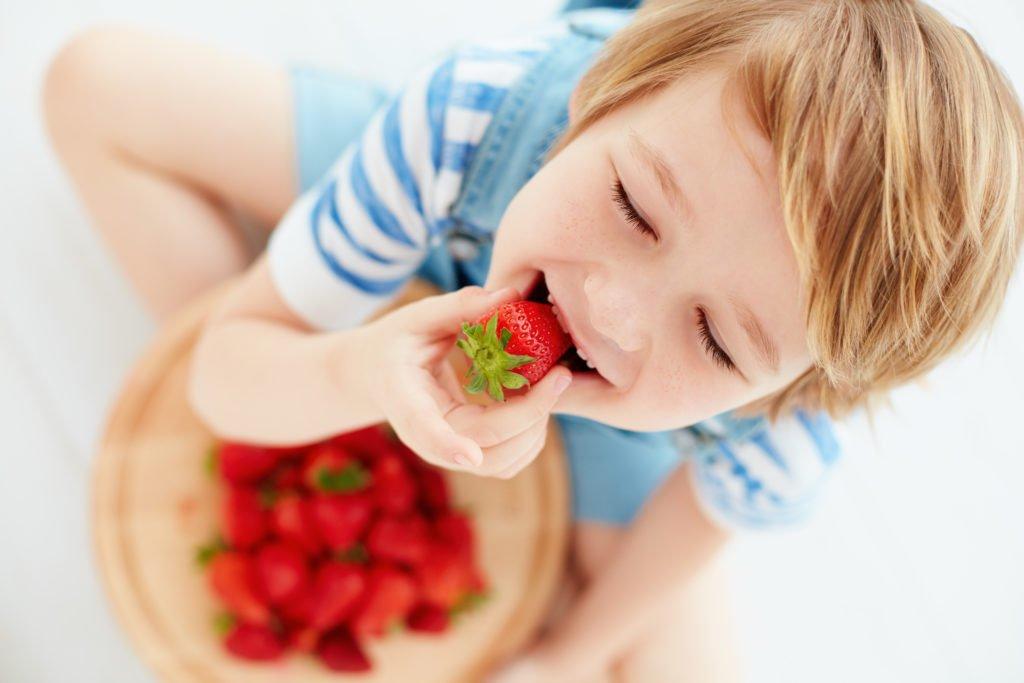 un enfant mange des fraises avec plaisir
