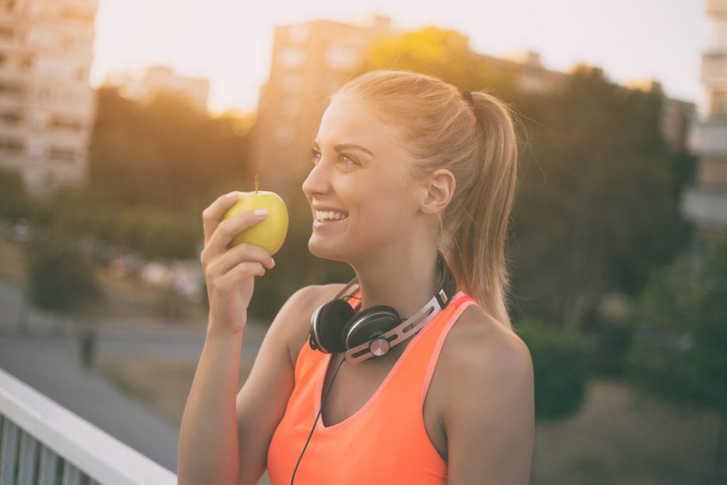 Une femme mange une pomme